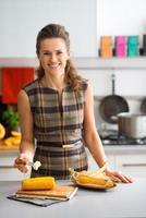 mulher elegante na cozinha sorrindo enquanto coloca manteiga na espiga de milho