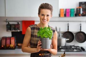 mulher sorridente na cozinha segurando o pote de manjericão fresco