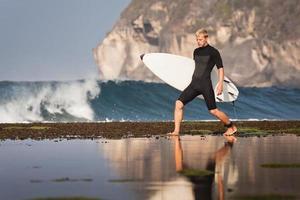 surfista com prancha de surf na praia foto