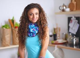jovem de pé na cozinha dela foto