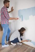 casal alegre pintando seu quarto de azul