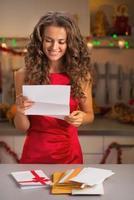 dona de casa feliz lendo a carta na cozinha decorada de Natal