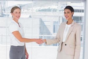 dois parceiros alegres, apertando as mãos foto