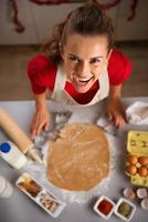dona de casa moderna fazendo biscoitos com tema de Natal na cozinha foto