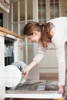 jovem mulher colocando pratos na máquina de lavar louça
