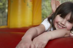 menina alegre, deitado no castelo inflável foto