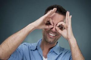 homem alegre, fazendo o gesto com a mão foto