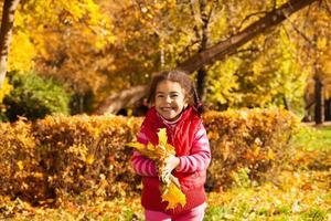 linda garota com um monte de folhas amarelas foto