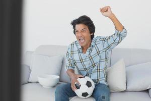 fã de futebol torcendo enquanto assiste tv