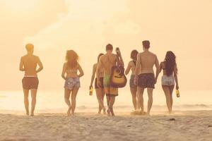 grupo de amigos caminhando na praia ao pôr do sol.