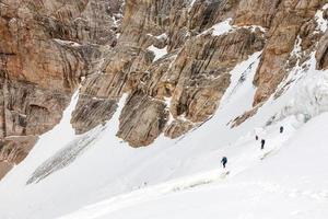 alpinistas ligados a glacie ascendente de corda de proteção foto