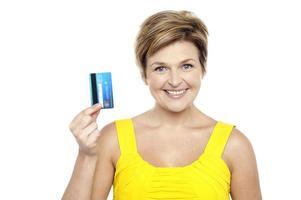 alegre mulher segurando seu cartão de débito foto