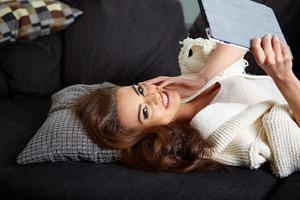 alegre mulher deitada em um sofá aconchegante foto