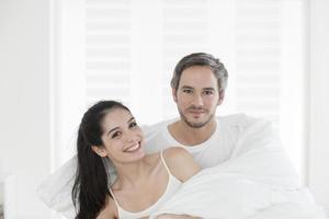 casal jovem alegre, embrulhado em sua colcha