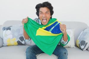 fã de futebol brasileiro torcendo enquanto assiste tv