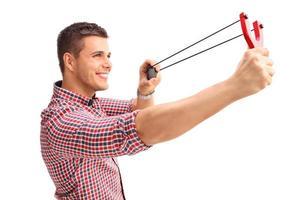 homem alegre atirando um estilingue e sorrindo foto