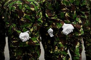 soldados em uniforme de camuflagem com as mãos atrás das costas