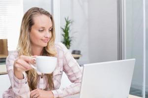 empresária alegre usando o notebook dela segurando uma xícara foto