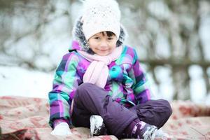 menina alegre no parque no inverno foto