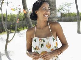 mulher alegre, inclinando-se contra palmeira na praia