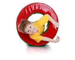 menino alegre brincando com um módulo redondo macio foto