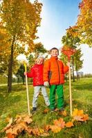 alegre menino e menina com ancinhos em pé no parque foto
