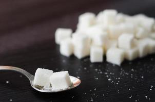 cubos de açúcar branco empilhados na pilha sobre a mesa preta foto