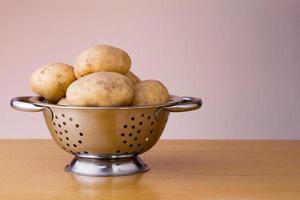 maris piper batatas em uma peneira foto