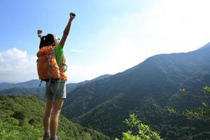 torcendo os braços abertos de alpinista de mulher no penhasco de pico de montanha foto