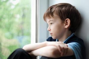 menino triste sentado na janela foto