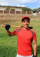 jogador de beisebol sorridente posa em um campo do parque foto
