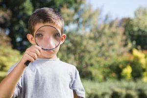 rapaz alegre, olhando através de uma lupa foto