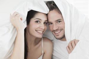 casal jovem alegre, embrulhado em sua colcha foto