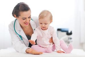 alegre bebê alto cinco para médico pediatra foto