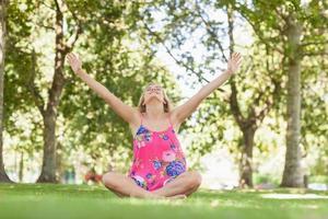 mulher loira alegre relaxante em um gramado