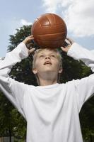 menino de pé com uma bola de basquete na cabeça. foto
