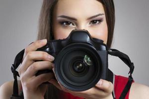 alegre mulher segurando a câmera fotográfica