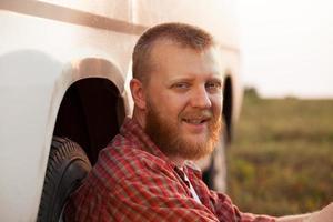 alegre homem sentado perto do carro foto