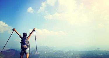 torcendo mulher caminhadas no pico da montanha foto