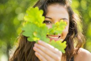 linda morena alegre segurando uma folha foto