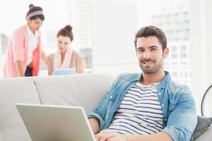 empresário alegre usando laptop no sofá foto