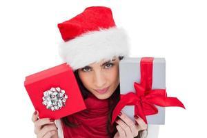 morena alegre segurando presentes de natal foto