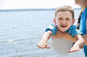 menino alegre brincando com sua mãe foto