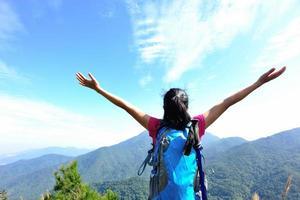 torcendo caminhadas mulher no pico da montanha foto