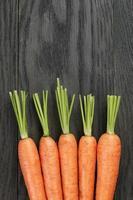 cenouras frescas na velha mesa de carvalho com espaço de cópia foto
