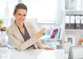 mulher de negócios feliz no escritório apontando no espaço da cópia foto