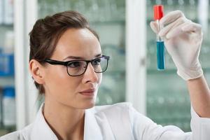 biólogo analisando o tubo de ensaio com líquido químico foto