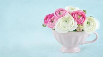 flores de ranúnculo em um copo rosa com espaço de cópia foto