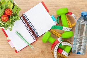 comida saudável, dumbells, fita métrica e bloco de notas para o espaço da cópia foto
