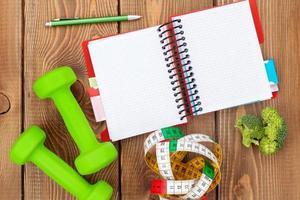 dumbells, fita métrica, comida saudável e bloco de notas para o espaço da cópia. foto